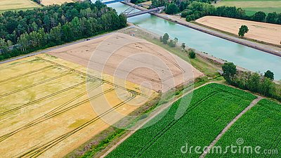 Aerial view of a canal that runs through fields, meadows and arable land in the flat landscape of northern Germany