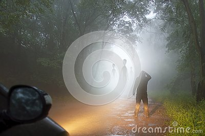 A science fiction concept of a man looking at aliens coming out the mist on a foggy, spooky forest road in the evening. Highlighte