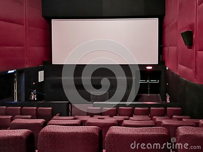 Cinema - interior of a movie theatre with empty red and black seats with white screen