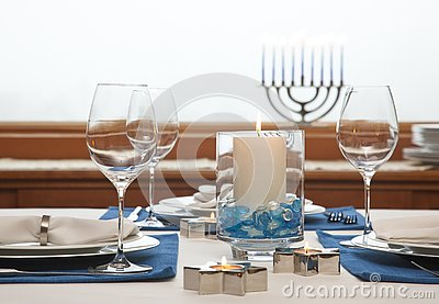 Dinner table setting decorated for Hanukkah. Traditional Jewish holidays home celebrations decor