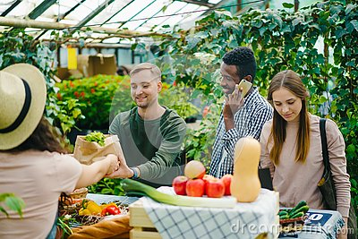 Group of customers choosing organic food in market talking to sales woman