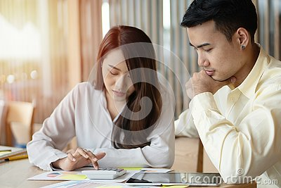 Unhappy Asian couples are calculating income And expenses To cut unnecessary expenses. Concepts for investment planning and financ