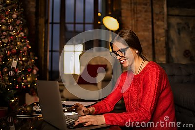 Happy smiling woman in fashionable glasses and casual wear skilled content writer typing text on laptop computer