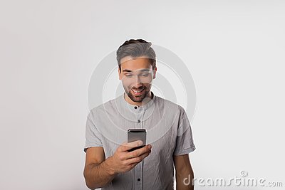 Happy smiling man in casual wear watching video on mobile phone while standing isolated in studio