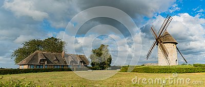 View of the historic windmill Moulin de Pierre and miller`s house in Hauville in Normandy