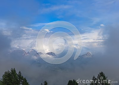 View from the top of the mountain to the peaks of the Dolomites covered in fog and clouds. Colfosco Calfosch