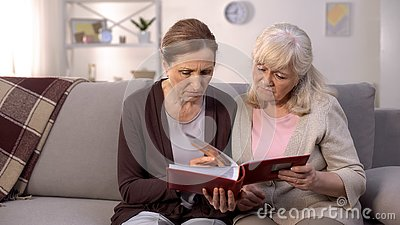 Upset women looking through photo album remembering past times, sad memories