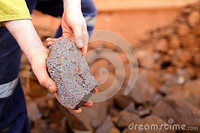 Scientist geologist hands inspecting exploration on iron ore rock on open field mine site