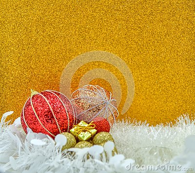 Christmas gift and baubles on golden background.