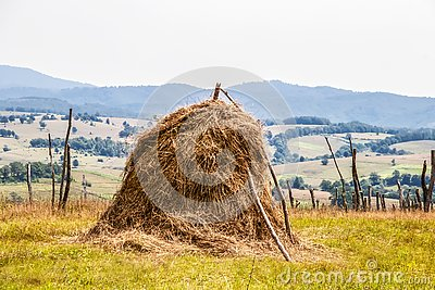 Old fashioned hay stack surrounded by stick fence with farm and hill countryside in the background - Georgia Eastern Europe