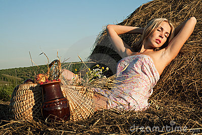 Beautiful woman sitting on the hay
