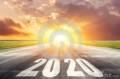 Road asphalt road with the inscription 2020 year with the rising sun in the morning. The concept of the beginning of new goals and