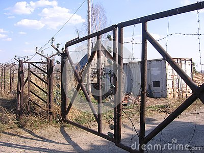 An old iron fence with a closed rusty gate prohibits travel to the territory of an abandoned technical station