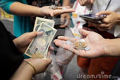 Osaka japan - november8,2018 : unidentified people counting japanese yen coint and banknote in osaka city market