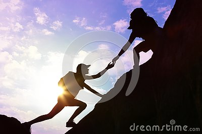 Silhouettes of man and woman helping each other to climb on hill