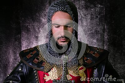 Portrait of handsome medieval knight in suit of armour with beard looking down in contemplation