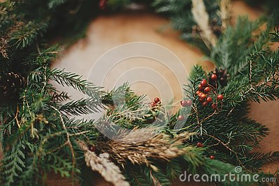 Rustic Christmas wreath detail closeup. Fir branches, pine cones, berries on wooden table. Authentic stylish still life. Making