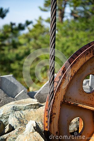 Steel cable and winch. Part of an old winch with a steel rope on a lift. Detail of the cableway. Close-up view of steel big wheel