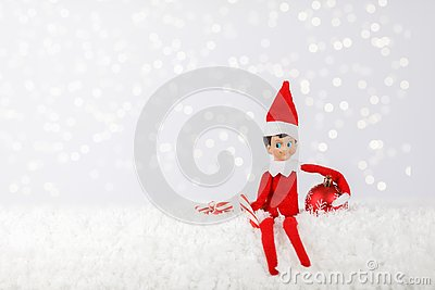 Christmas Elf sitting on a Snowy Shelf with Peppermint Sticks and Ornament