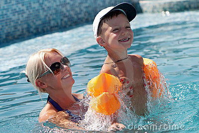 Woman and little boy bathes in pool