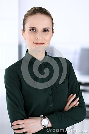 Business woman headshot in modern office. Secretary or female lawyer standing straight and looking at camera. Business