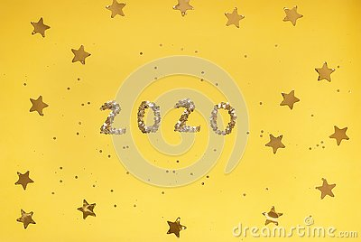 2020 numbers from small confetti with shining stars . Festive background. New Year. Top view.