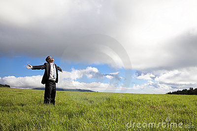 Relaxation businessman standing on the green field