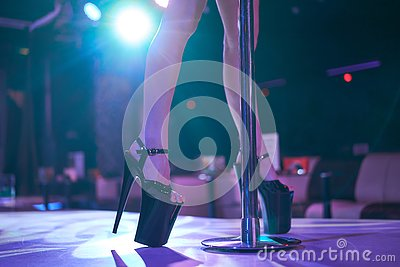 Young sexy woman pole dancing striptease with pylon in night club. Beautiful naked stripper girl on stage. Beautiful