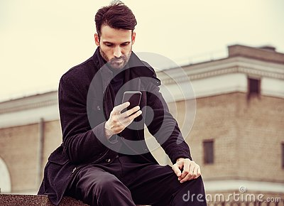 Serious thinking business man in fashion clothing texting sms looking on mobile phone in the hand outdoors autumn background