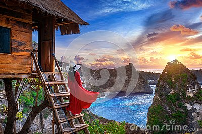 Young girl on steps of house on tree at sunrise in Nusa Penida island, Bali in Indonesia