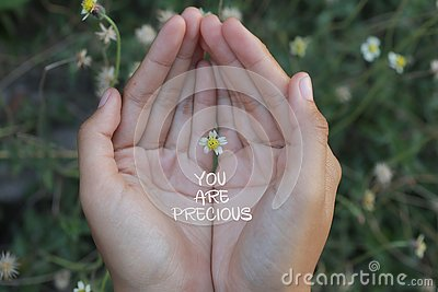 Inspirational quote - You are precious. With beautiful tiny flower in hand. Self love and care concept.