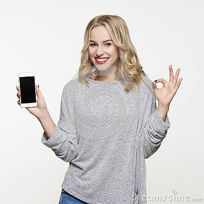 Happy young woman showing mobile phone with blank screen over white background, making ok sign with her hand.