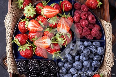 Organic strawberries, raspberries, blueberries, blackberries on a separate dish close-up on a solid concrete background.