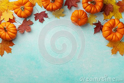 Autumn Thanksgiving background. Pumpkins and maple leaves on turquoise table top view