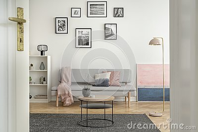 Small round wooden coffee table in front of trendy sofa in elegant interior