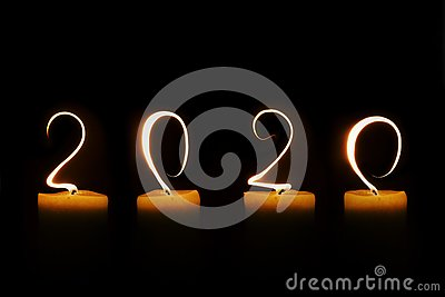 2020 written with candle flames on black background greeting card