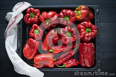 Red peppers on a tray ready to bake. Top view