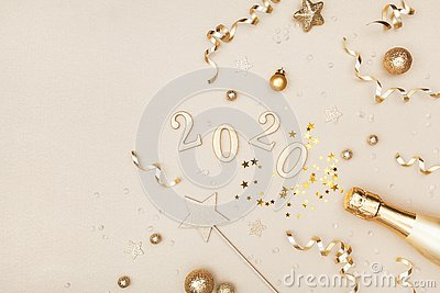 Celebration Christmas and New Year background with golden champagne bottle, holiday decoration, confetti stars and 2020 numbers.