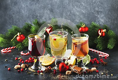 Mulled wine and mulled cider. Hot winter drinks and cocktails for christmas or new year`s eve in glass mugs with spices and citru