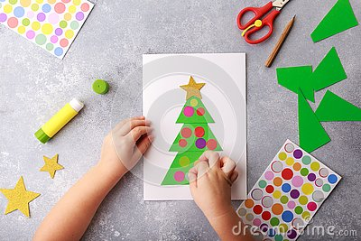 The child makes a greeting card Christmas paper collage. Children`s art project craft for kids