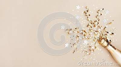 Celebration background with golden champagne bottle, confetti stars and party streamers. Christmas, birthday or wedding. Flat lay