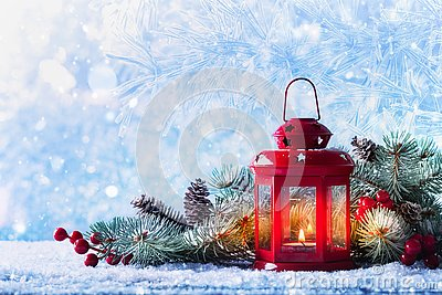 Christmas lantern in snow with fir tree branch. Winter cozy scene