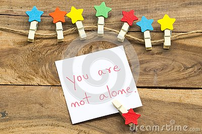 You are not alone message card handwriting with colorful wooden star clips arrangement flat lay postcard style