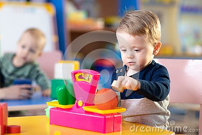 Cute little boy playing with abacus in nursery. Preschooler having fun with educational toy in daycare or creche. Smart