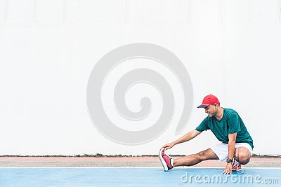 Young asian man stretching legs before run with copy space