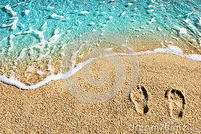 Two footprints on yellow sand, blue sea wave, white foam top view close up, turquoise ocean water, summer vacations concept