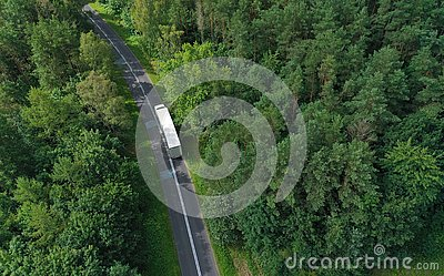 Aerial drone perspective view on white truck with cargo trailer riding through the forest on curved asphalt road
