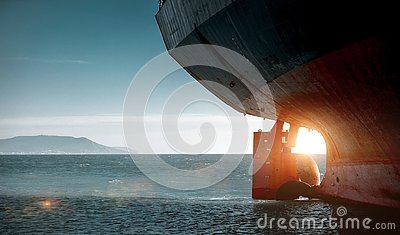 Stern of a cargo ship aground against backdrop of blue sea. World Transport Problems Freight Shipping Concept