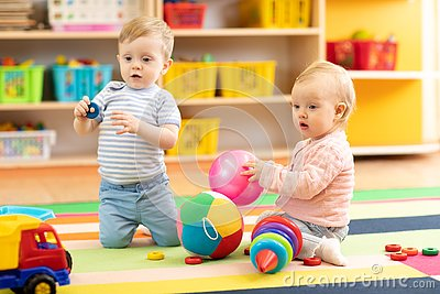 Babies boy and girl playing on floor with toys. Kids toddlers in creche or nursery