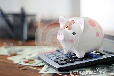 Abstract sick and injured piggy bank standing on calculator among money and coin on table in office. business financing accounting